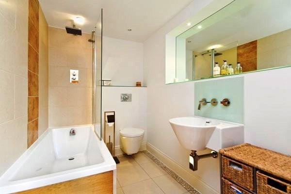 rectangle white bathtub and white latrine also grey fur mat on beige wooden floor