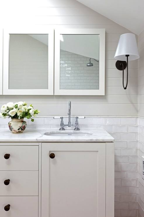 Black wood framed mirrors balance well with a white dual washstand Accented with antique brass knobs and off white quartz countertop