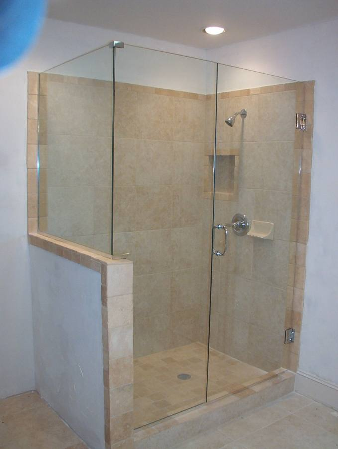glass shower room with sliding door connected by stainless steel shower on wall tile