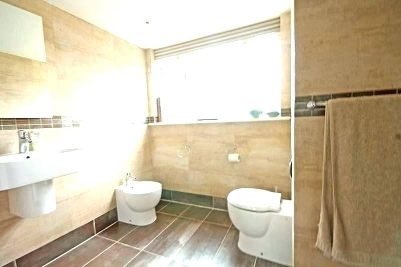white toilet and sink on the brown floor combined with brown white bath up