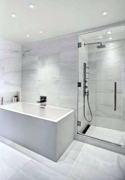 rectangle white bathtub in glass shower stalls with stainless shower on grey tile wall