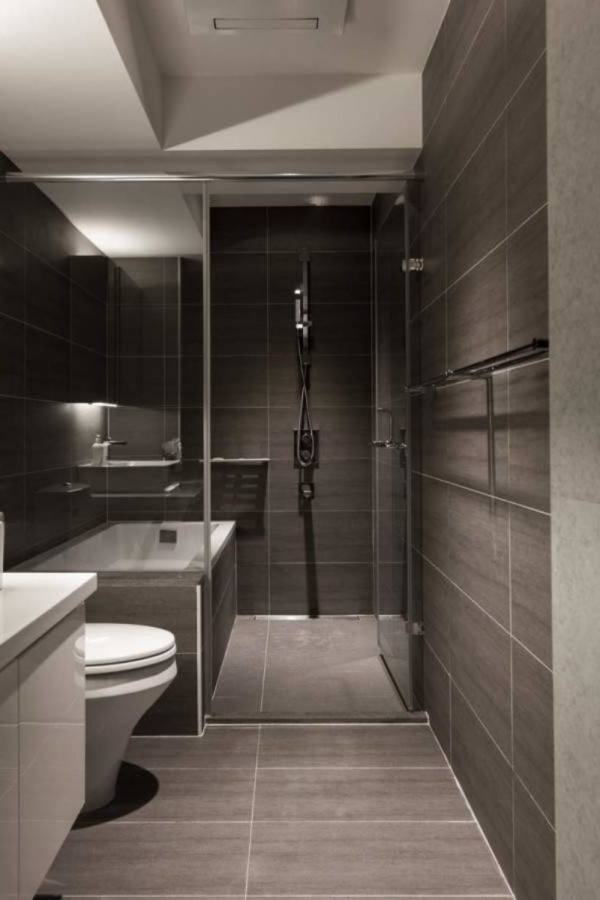 rectangle white bathtub with black tile connected by black tile wall