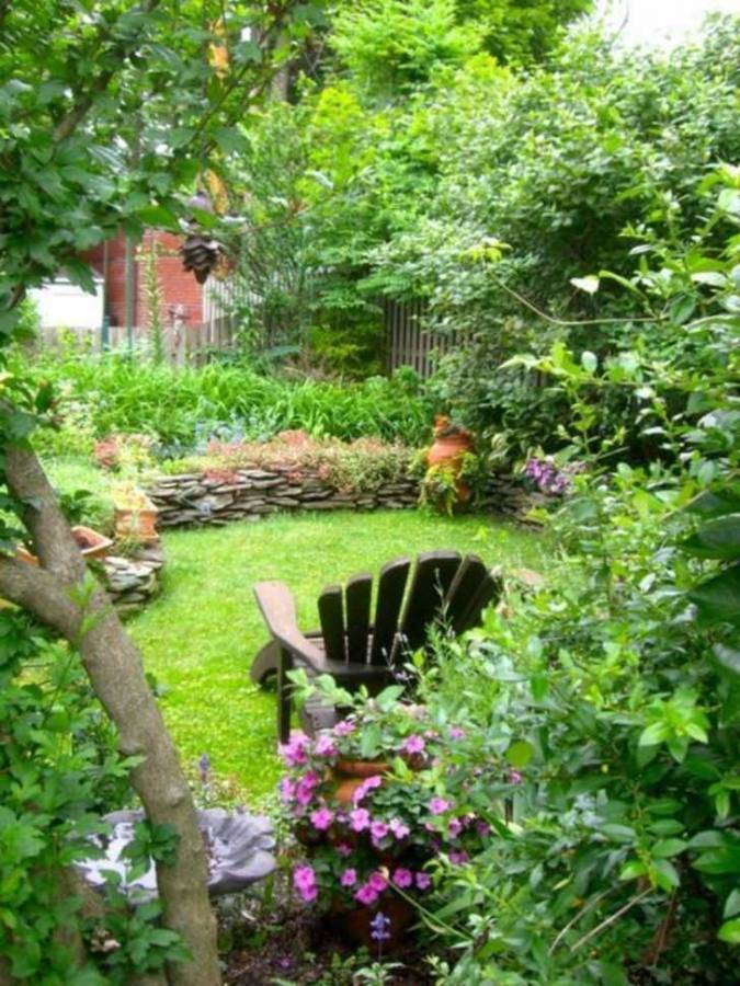 backyard with a fascinating fountain decorated with flowers and different types of plants