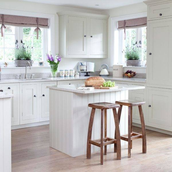 cream wooden cabinet and kitchen island with brown counter top completed with white wooden