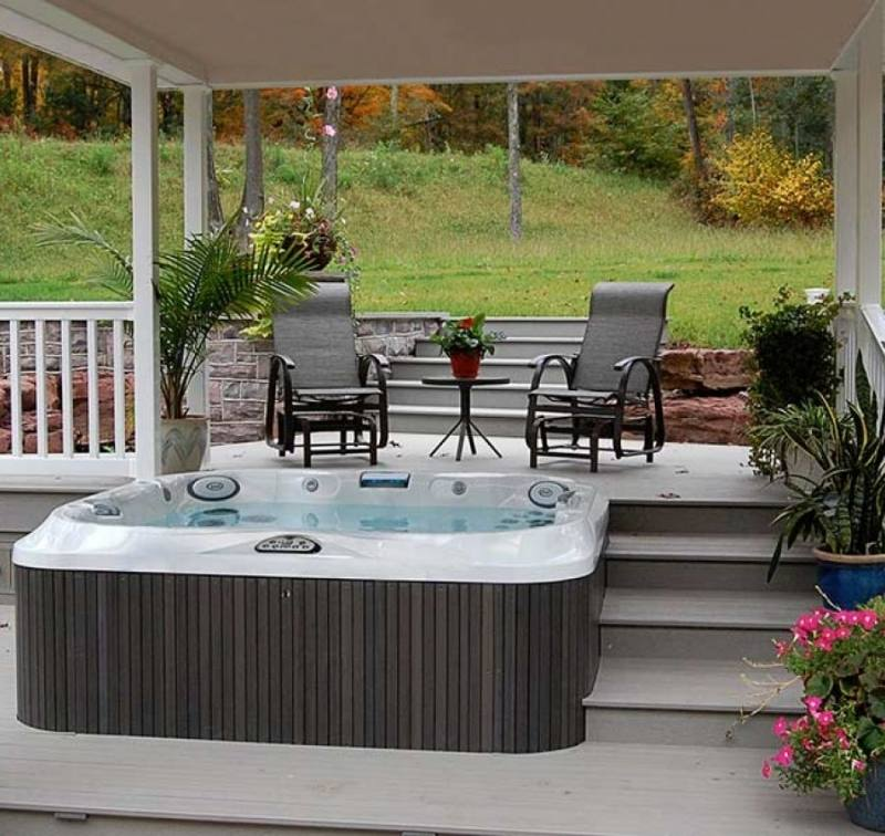 Outdoor living poolside including spa with copy space on pool deck