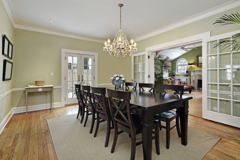 Chic cottage dining room features a farmhouse dining table lined with black  salt Chairs illuminated by a Thomas O'Brien Bryant Chandelier