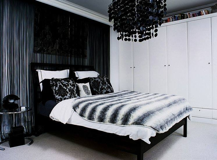 Go monochrome in your bedroom by decorating a black bed with white decorative pillows