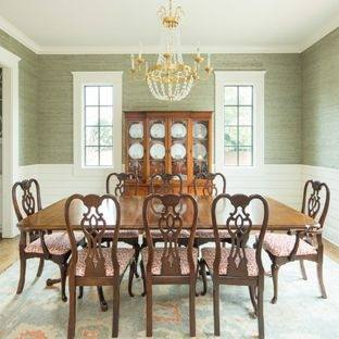 Wooden dining  table and chairs combine with chandelier and red rose on the table makes  this